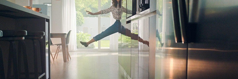 Menina pulando em uma cozinha